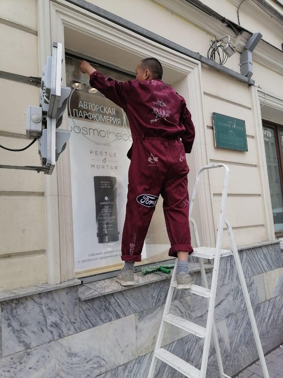 Нанесение раствора для мытья витрины магазина